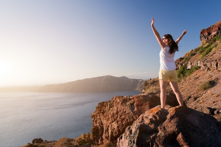32104201 - happy woman on the rock with hands up. santorini island, greece, view on caldera and aegean sea at sunset. winner, success, active, travel concepts